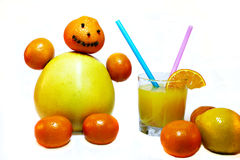 Little man made of citrus fruits. Cheerful man made of pomelo tangerines with a glass of orange juice Stock Images