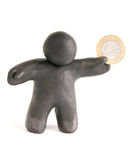 The little man with the one euro coin made from plasticine. The plasticine man holding a one euro coin in his hand on a white background Stock Photography
