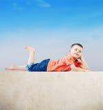 Little man relaxing after tiring play. Little boy relaxing after tiring play Stock Photo