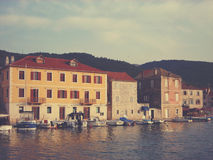 Little marina with moored boats and traditional architecture on Hvar island Stock Image