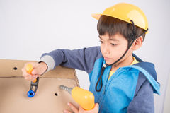 Little mechanic fixing the paper house. Little boy pretend as a mechanic use tools fix the paper house Royalty Free Stock Image