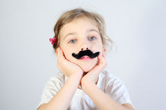 Little melancholy girl with glued fake mustache. Little melancholy girl in white with glued fake black mustache royalty free stock photography