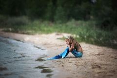 Little mermaid on the beach. The little dream mermaid girl on the beach is looking on the ocean royalty free stock photo