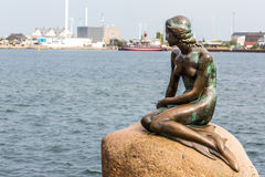 The Little Mermaid is a bronze statue by Edvard Eriksen, depicting a mermaid. The sculpture is displayed on a rock by the. Waterside at the Langelinie promenade royalty free stock photography