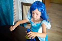 The little mermaid girl. Is interested in science. She sits at a large wooden table, looks through a microscope, studying biology and microbes. Blue dress and royalty free stock image