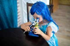 The little mermaid girl. Is interested in science. She sits at a large wooden table, looks through a microscope, studying biology and microbes. Blue dress and royalty free stock images