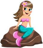 Little mermaid que se sienta en la roca Imagenes de archivo
