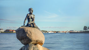 Little Mermaid statue on rock in Denmark. Front view of Little Mermaid statue on large boulders in Denmark with harbor under blue sky in the background royalty free stock photo