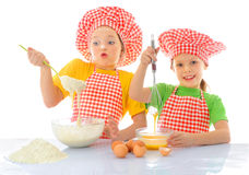 Little messy bakers. Two ittle messy girls kneading dough Royalty Free Stock Photography