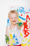 Little messy kid painting with paintbrush picture on easel. Education. Creativity. School. Preschool. Studio portrait over white b Royalty Free Stock Image