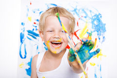 Little messy kid painting with paintbrush picture on easel. Education. Creativity. School. Preschool. Studio portrait over white b Stock Photography