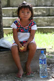 Little mexican girl. A little Mexican girl with backlight is sitting eating a piece of bread or cake. On the ground next to her, there is a plastic bottle Stock Image