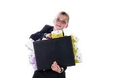 Little millionnaire. A teenage boy wearing a dark suit and tie, holding a briefcase full of cash in hand, smiling and looking at the camera Stock Images