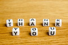 Little miniature figurines with little dices forming word thank you as a part of team meeting collection pictures