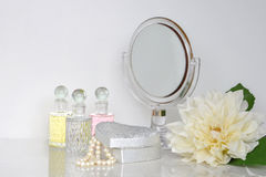 Little mirror on a dresser rounded with fragrance bottles and casket. With pearls Stock Image
