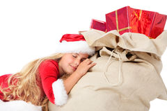Little miss santa asleep on the sack of gifts. Miss santa sleeping on the sack of gifts and dreaming on white Royalty Free Stock Photo