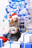 Little miss Santa holds disco ball. Winter holiday and party. Concept. Girl with smiling face near white and blue Christmas tree on white background. Kid in stock image