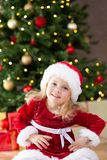 Little miss santa smiling in front of the christmas tree stock images