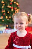Little miss santa smiling in front of the christmas tree royalty free stock photo