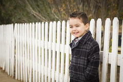 Little Mixed Race Boy Waiting For School Bus Along Fence Outside Stock Photography