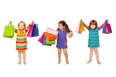Little modeflickor med shoppingpåsar Arkivfoto