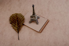 Little model Eiffel Tower, notebook and a dry leaf Royalty Free Stock Photo