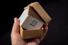 Little model house in hand in a box. Little model house in hand in a paper box Stock Photos