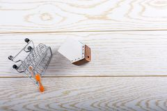 Little model house on a parquet background. Little model house and a trolley and on a parquet background Stock Photography