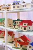 Little models of cottages stand on shelves Stock Photos