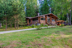 Little modern log cottage in a beautiful quiet location on the background of pines Stock Photo