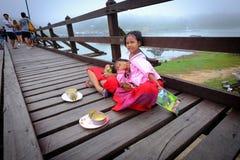 Little Mon selling on the wooden bridge. Stock Photo