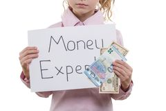 Little money specialist, child girl with cash bills of dollar and euro holding white sheet of paper with text money expert, white royalty free stock photos