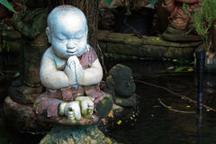 Little monk statue. Decor in a pool of a Thai ' temple Royalty Free Stock Photos