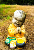 Little monk statue on grass Stock Image