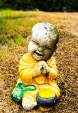 Little monk statue on grass Stock Image