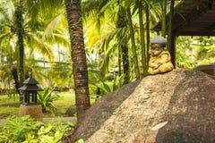 Little monk statue sitting on rock Stock Image