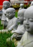 Little monk statues. Scatter on a field Stock Image
