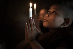 Little monks praying. With candlelight Royalty Free Stock Photo