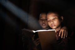 Little monks reading book. Inside monastery royalty free stock photo