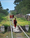 Little monks on their alms round. Walking on a railway. Mandalay, Myanmar royalty free stock image