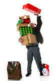 A Little More. Man in a Santa hat holding a precarious stack of wrapped Christmas gifts while attempting to pile on yet another Royalty Free Stock Photos