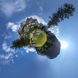 Little mountain planet in the sky. Little mountain  panorama planet with cloudy sky, pine trees and creek Royalty Free Stock Photography
