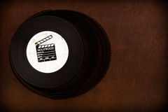 Little movie clapper board on 35 mm film reel Stock Photo