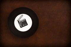 Little movie clapper board on 35 mm film reel Royalty Free Stock Photography