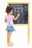 Little mulatto girl draws on the board royalty free stock images