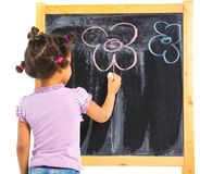 Little mulatto girl draws on the board Stock Image