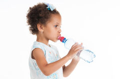 The little mulatto girl drinks water from a bottle Stock Photo