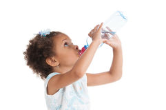 The little mulatto girl drinks water Royalty Free Stock Images
