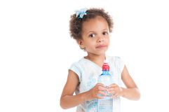 The little mulatto girl drinks water from a bottle Royalty Free Stock Images