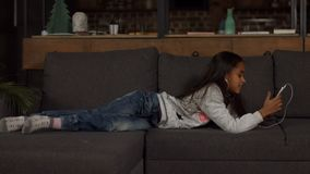 Cute african american girl listening music on couch stock footage